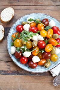 Tomatensalat mit Mozzarella, Oliven und Rucola